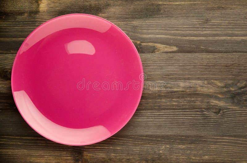 Plaat op een houten achtergrond plaat hoogste mening De ruimte van het exemplaar Roze stock foto