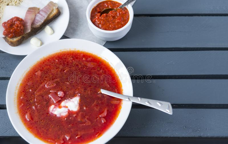 Plaat van borscht, ketchup, reuzel op een stuk van brood op een houten grijze achtergrond stock afbeelding