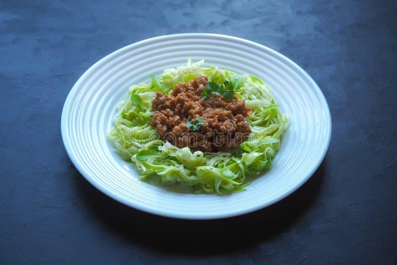 Plaat van courgettespaghetti met rundvlees bolognese op zwarte achtergrond royalty-vrije stock afbeeldingen