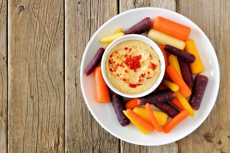 Plaat van de wortelen van de babyregenboog met hummus op rustiek hout stock foto's