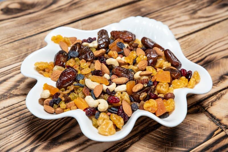 Plaat van droge vruchten op houten lijst, Mengeling van noten en bessen: rozijnen, hazelnoot, cachou, gele amandelen, droge Ameri stock afbeelding