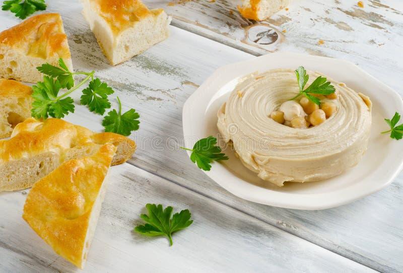 Plaat van een Gezonde Eigengemaakte Romige Hummus met pitabroodje stock foto