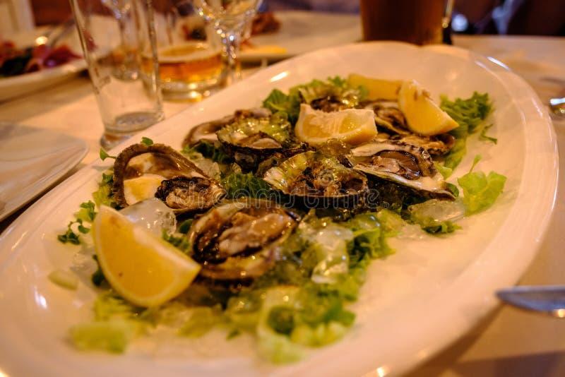 Plaat van gekookte oesters op een bed van salade stock fotografie