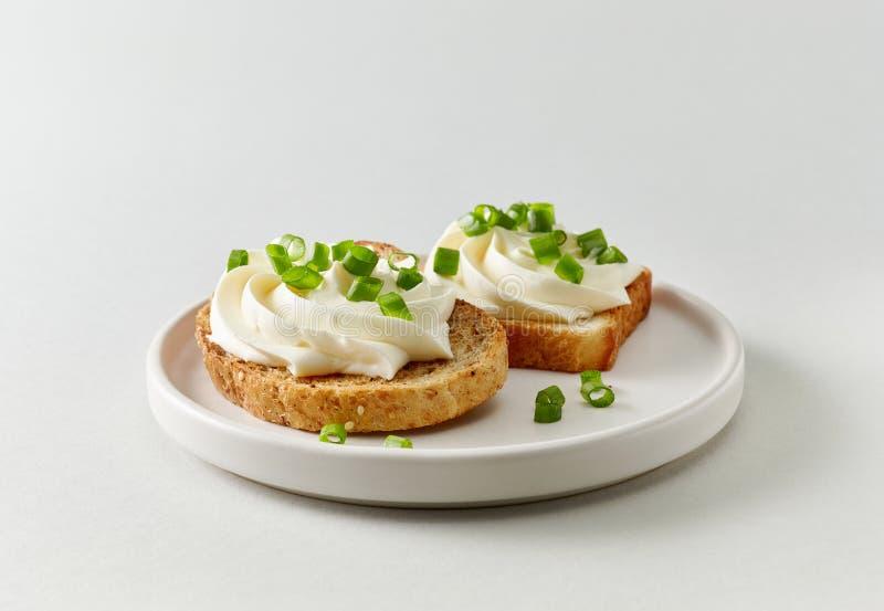 Plaat van geroosterd brood met roomkaas stock fotografie