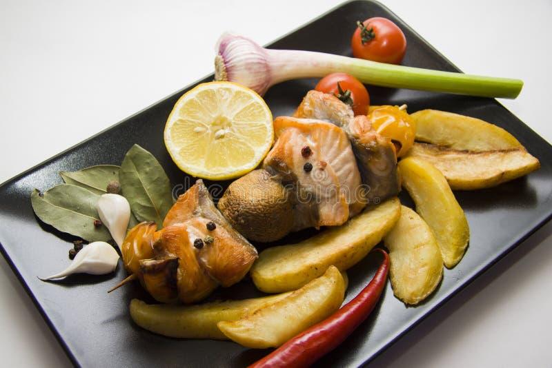 Plaat van geroosterde vissen met geroosterde aardappel royalty-vrije stock foto's