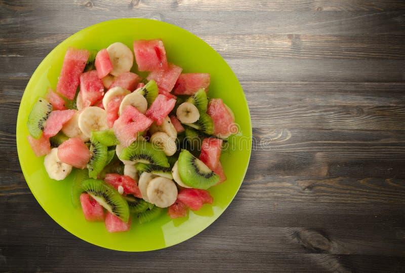 Plaat van gezonde verse fruitsalade op houten achtergrond stock fotografie