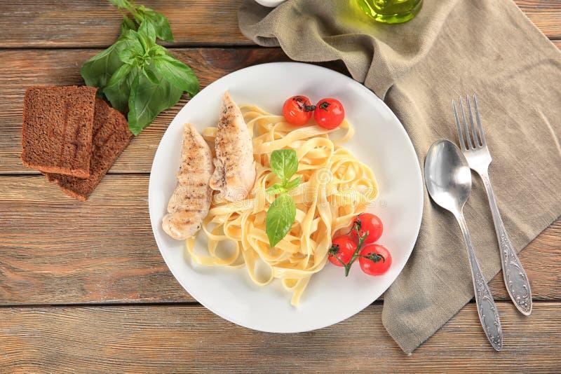 Plaat van heerlijke deegwaren met geroosterde kippenfilet en tomaten op lijst, hoogste mening stock foto