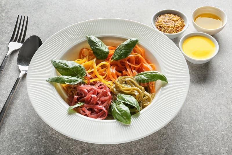 Plaat van heerlijke kleurrijke deegwaren en kommen met sausen op lijst stock foto's