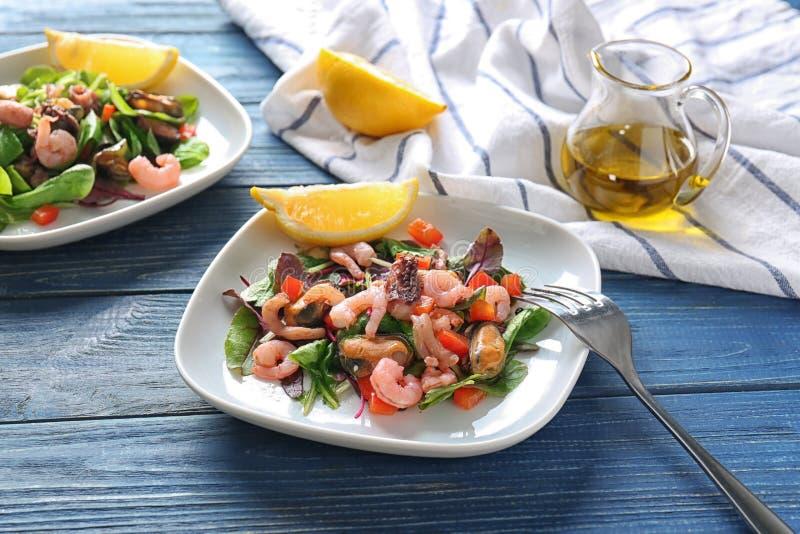 Plaat van heerlijke plantaardige salade met zeevruchten op houten lijst stock fotografie