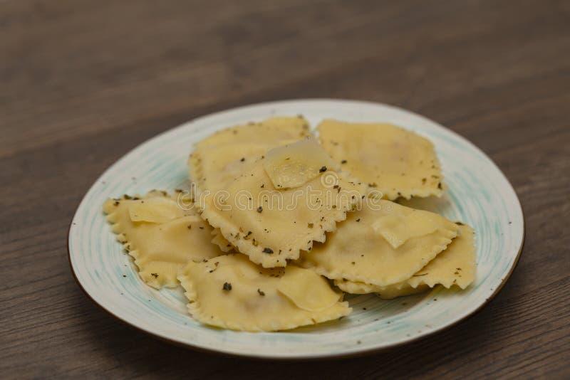 Plaat van ravioli met Parmezaanse kaas op houten lijst stock fotografie