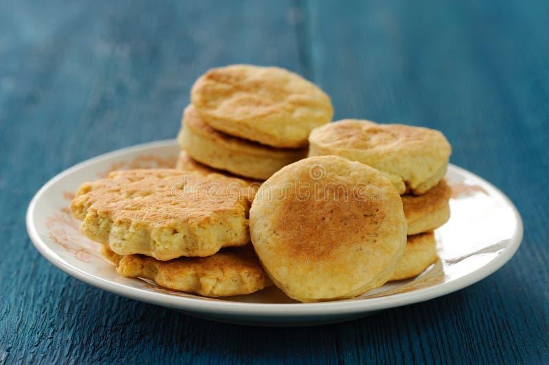 Plaat van smakelijke onvolmaakte eigengemaakte koekjes op diepe blauwe backgroun stock foto