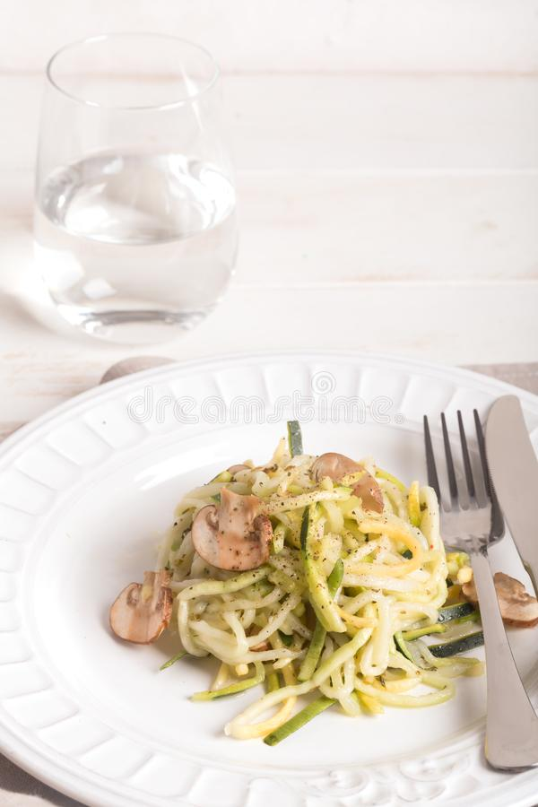 Plaat van spaghetti van courgette en paddestoelsaus op houten lijst wordt voorbereid die royalty-vrije stock foto