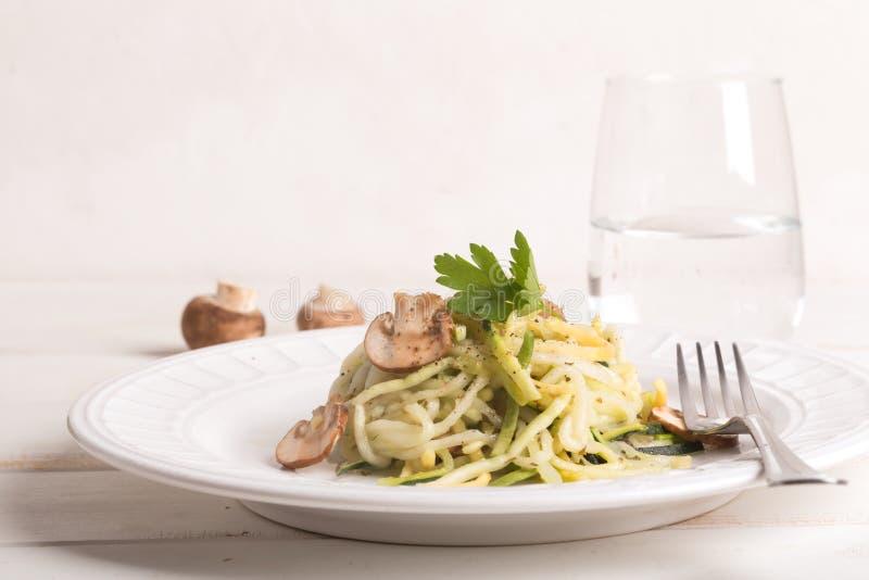 Plaat van spaghetti van courgette en paddestoelsaus op houten lijst wordt voorbereid die royalty-vrije stock foto's