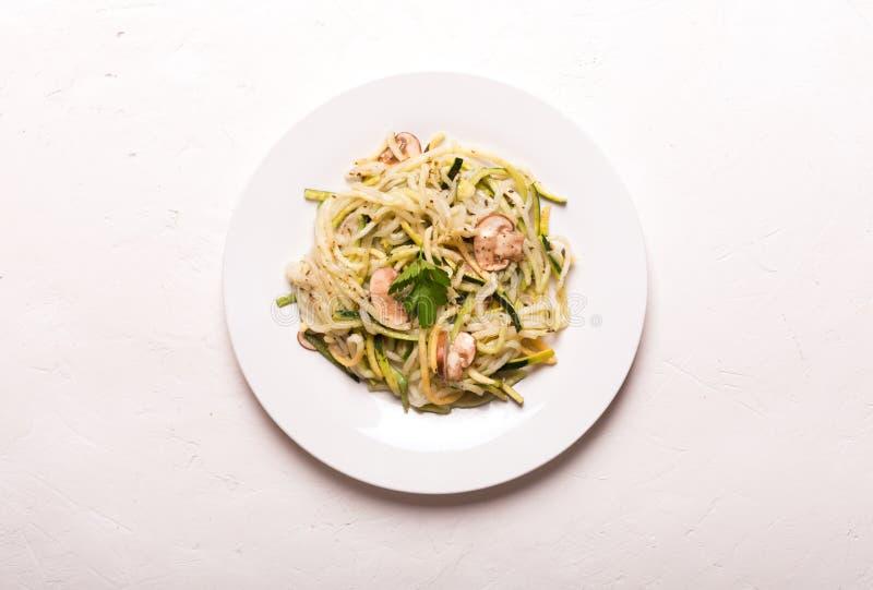 Plaat van spaghetti van courgette en paddestoelsaus op houten lijst wordt voorbereid die stock afbeeldingen