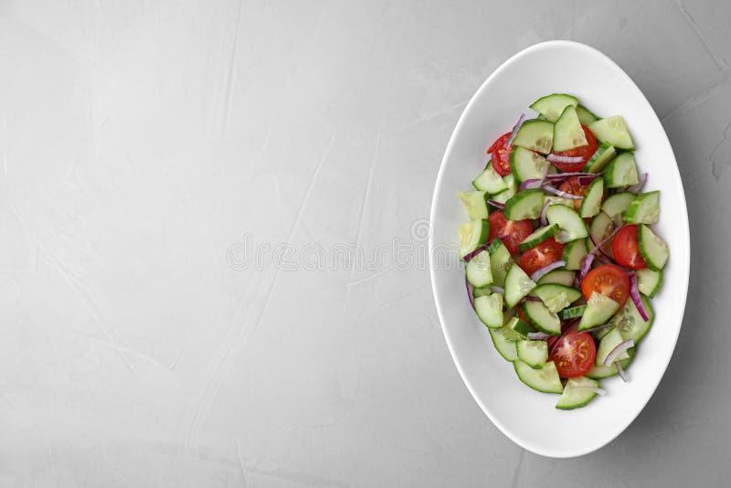 Plaat van vegetarische salade met komkommer, tomaat en ui op lichte achtergrond Ruimte voor tekst stock foto's
