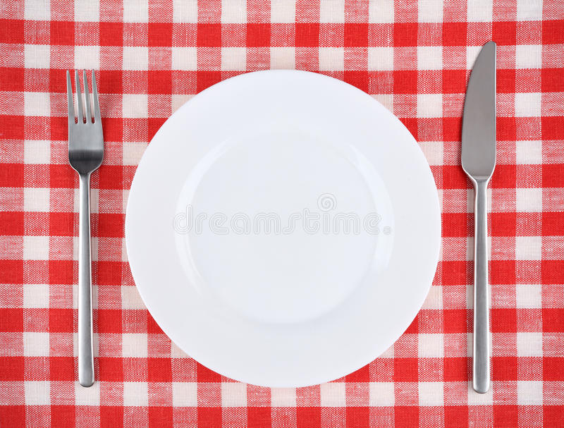 Plaat, vork, mes op een rood geruit tafelkleed stock afbeeldingen