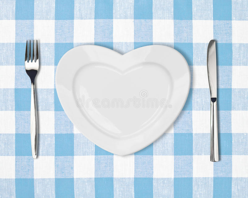 Plaat in vorm van hart, lijstmes en vork op blauw tafelkleed