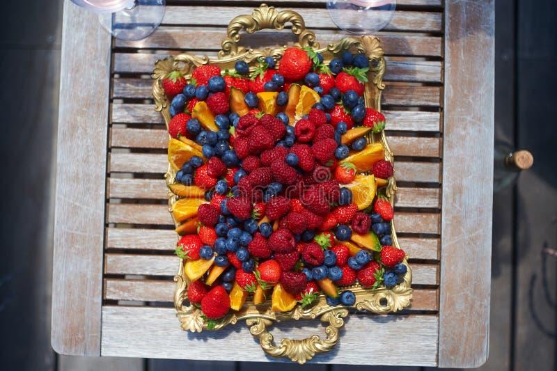 Plaat, vruchten, frambozen, sinaasappel, aardbei houten lijst stock foto