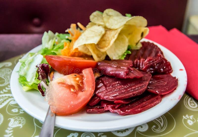 Plaathoogtepunt van heerlijk voedsel - chips, tomaten, groene salade en biet stock foto's