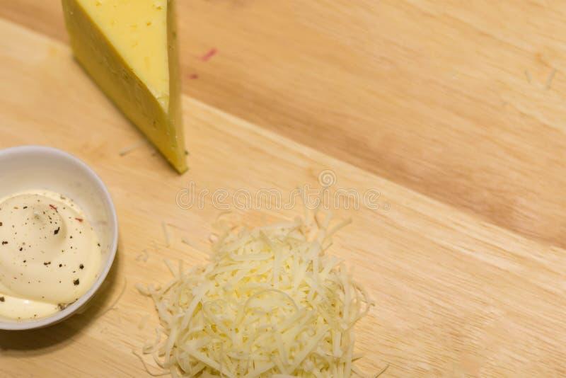 Plaats een stuk van kaas geraspte de zure roommayonaise van de sausbasis peppered zout op een houten basis royalty-vrije stock fotografie