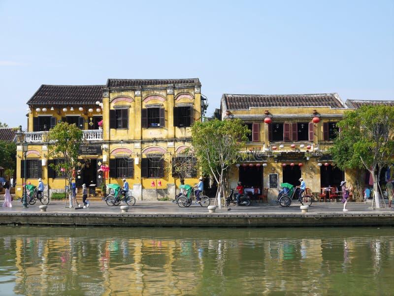 Plaatselijke bevolking, boten, gele huizen door de rivier, en toeristen in de oude stad van Hoi An stock foto's