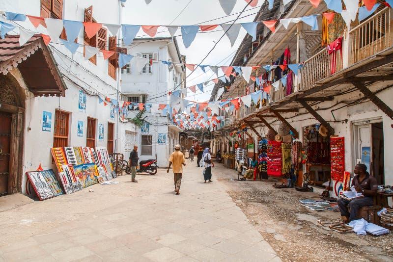 Plaatselijke bevolking op een vierkant in Steenstad De steenstad is het oude deel van de Stad van Zanzibar, de hoofdstad van Zanz stock afbeeldingen