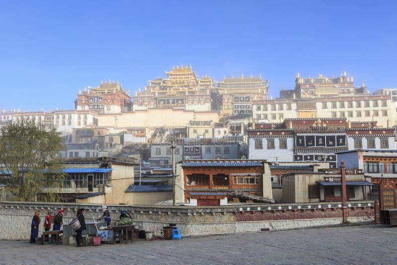 Plaatselijke bevolking voor de Songzanlin-Tempel, het Klooster van Ganden Sumtseling, een Tibetaans Boeddhistisch klooster in Zho stock afbeelding
