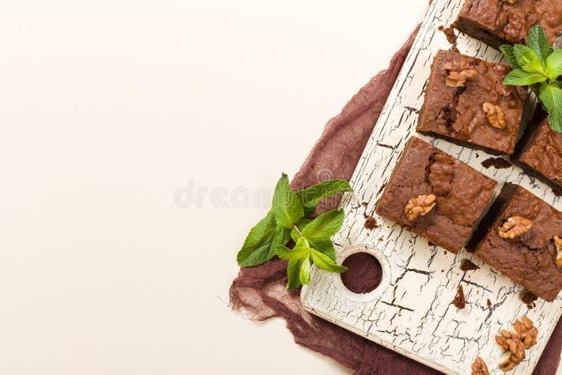Plaatsen het dessert van de brownie zoete chocolade met okkernoten en de bedoelde bladeren op retro raad met exemplaar op pastelk stock illustratie