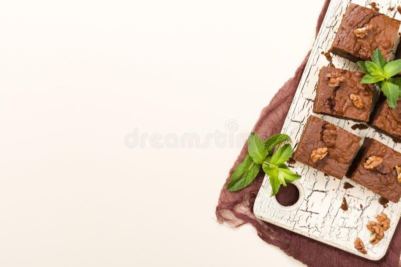 Plaatsen het dessert van de brownie zoete chocolade met okkernoten en de bedoelde bladeren op retro raad met exemplaar op pastelk royalty-vrije illustratie