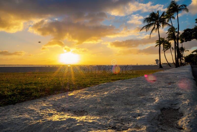 Plaatsend zon over strand bij Ala Moana Park, met gloed stock fotografie