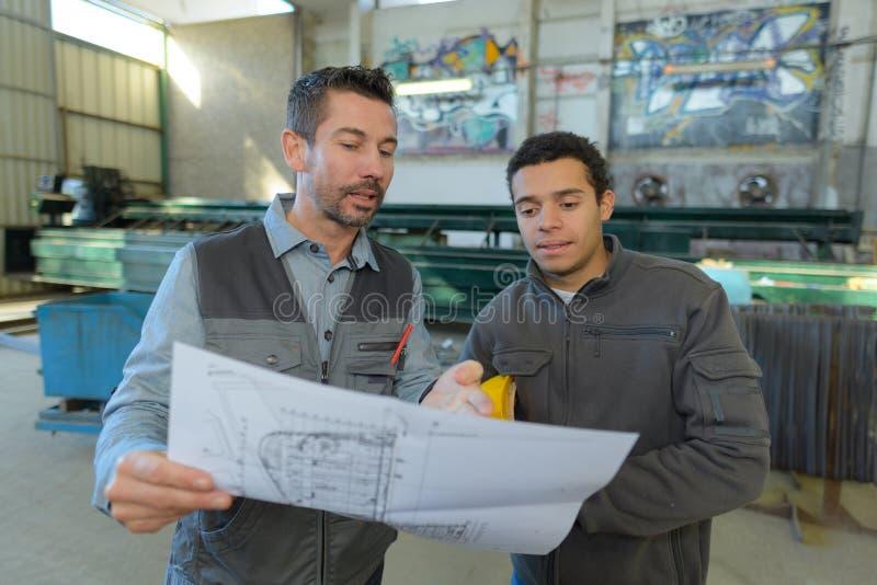 Plaatsinspecteur die inspectierapport in industriële zaal maken royalty-vrije stock afbeeldingen
