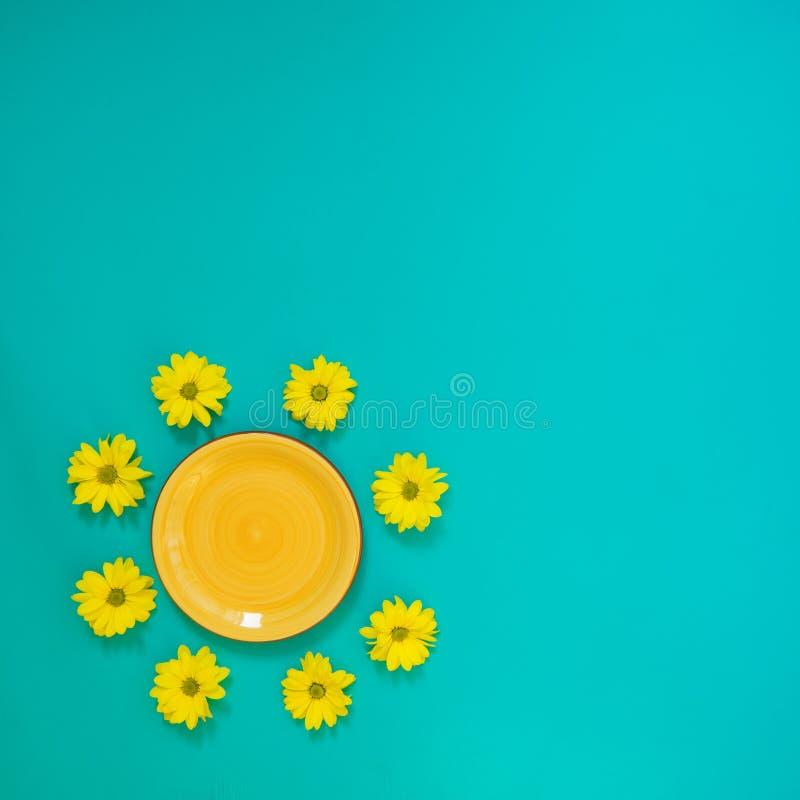 Placa amarela cercada por flores amarelas do crisântemo imagem de stock