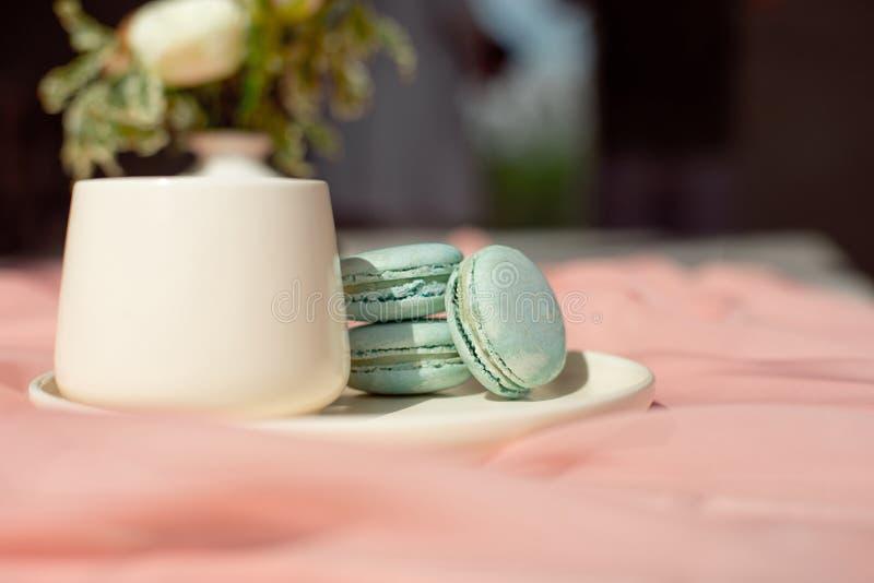 Placa azul de los macarrones franceses en la situación de la taza del rosa y de café en una tabla de madera con el florero blanco imagen de archivo libre de regalías