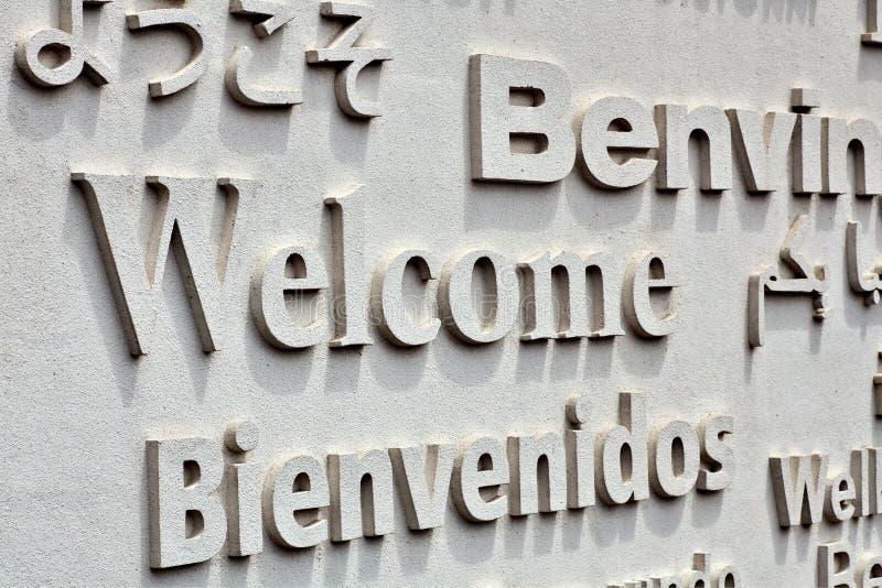Placa bem-vinda com cumprimento em línguas estrangeiras imagem de stock