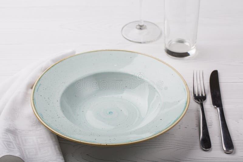 Placa, bifurcación, cuchillo y copas de vino vacíos en la tabla blanca fotos de archivo libres de regalías
