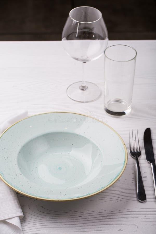 Placa, bifurcación, cuchillo y copas de vino vacíos en la tabla blanca foto de archivo