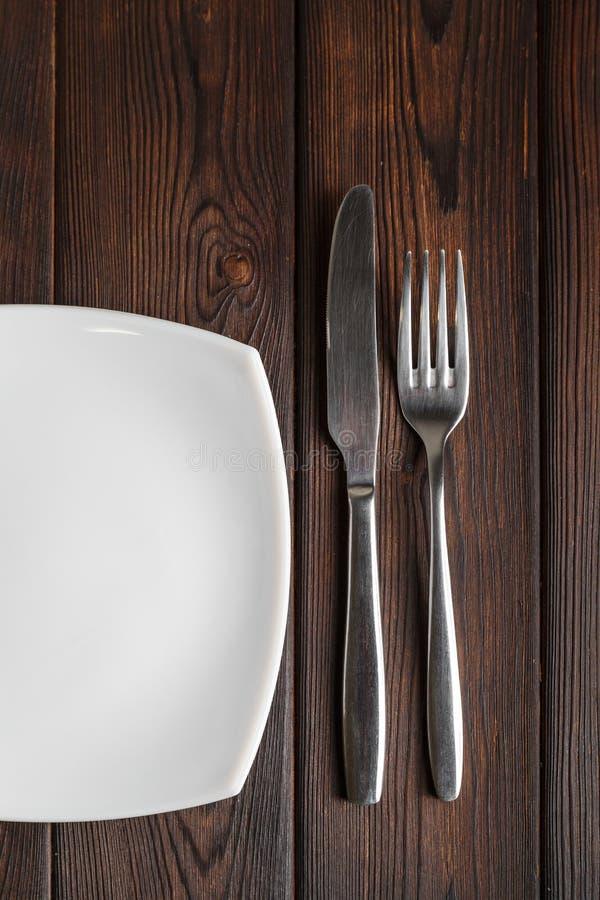 Placa, bifurcación y cuchillo vacíos en fondo de madera oscuro foto de archivo libre de regalías