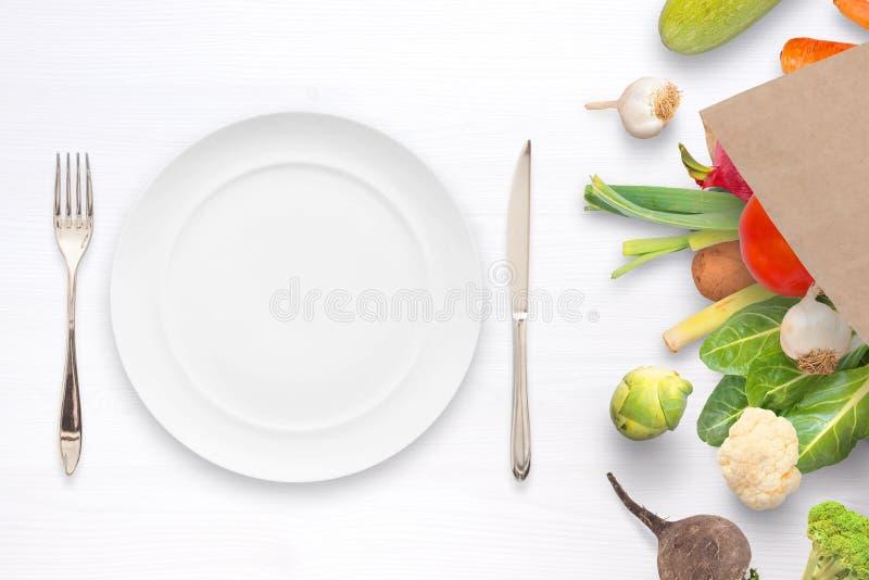 Placa, bifurcación y knige vacíos en la tabla con las verduras en bolsa de papel por otra parte fotos de archivo libres de regalías