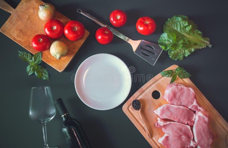 Placa blanca como espacio de la copia, carne de cerdo cruda fresca, la botella de vino tinto, la copa de vino y verduras frescas foto de archivo