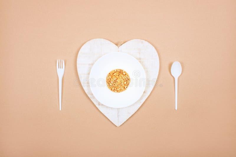 Placa blanca con la cuchara, la bifurcación y la harina de avena entera de las galletas del grano Dieta quetogénica, pérdida de p imagen de archivo