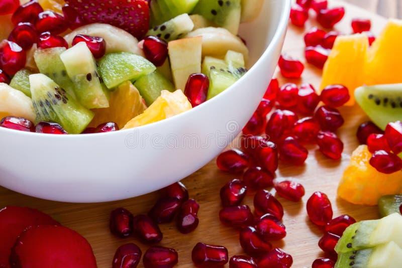 Placa blanca con la ensalada de fruta en una tabla de cortar imagen de archivo libre de regalías