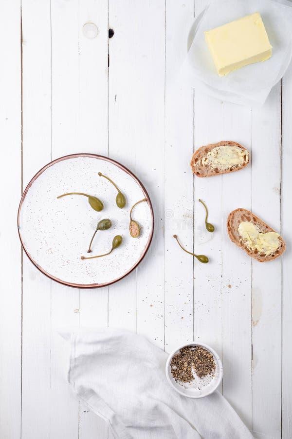 Placa blanca con las alcaparras, el pan con mantequilla y las especias en un fondo de madera blanco, visión superior fotografía de archivo