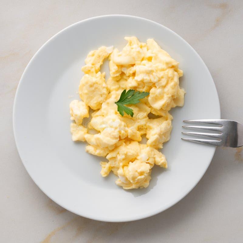 placa blanca con los huevos revueltos cacerola-fritos en fondo de la luz blanca con los tomates Tortilla, visión superior foto de archivo libre de regalías