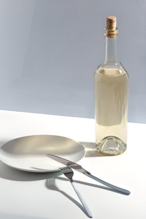 Placa blanca, cubiertos y una botella de vino blanco en una tabla brillante Concepto minimalistic de Cretive fotografía de archivo libre de regalías