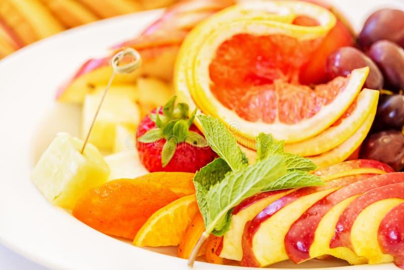 Placa blanca de las frutas con la fresa, el pomelo, las uvas, la naranja, las hierbas y el queso Ciérrese encima de imagen con el imagenes de archivo