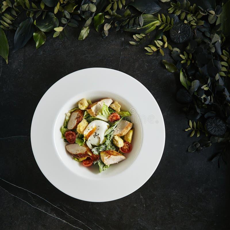 Placa blanca de servicio exquisita del restaurante del pollo y de las anchoas hechos en casa César o Cesar Salad imágenes de archivo libres de regalías
