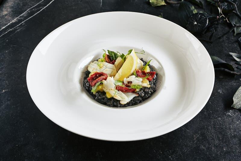 Placa blanca de servicio exquisita del restaurante del Risotto negro con la carne del pulpo, de las jibias o del calamar imagen de archivo libre de regalías