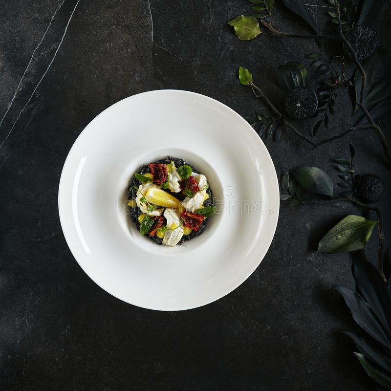 Placa blanca de servicio exquisita del restaurante del Risotto negro con la opinión de top de la carne del pulpo, de las jibias o fotos de archivo