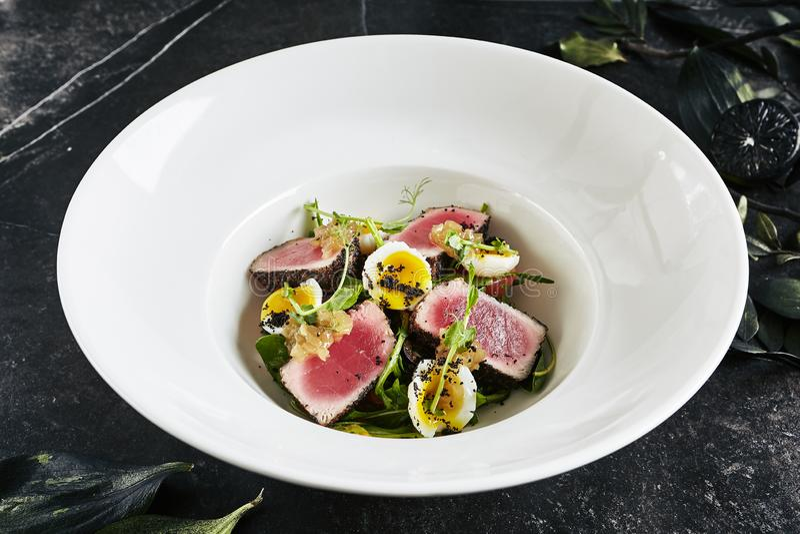 Placa blanca de servicio exquisita del restaurante de Tuna Fillet Salad con los huevos y la salsa de codornices de los tomates du fotografía de archivo
