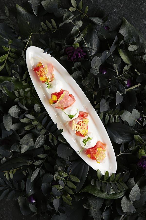 Placa blanca de servicio hermosa del restaurante del agua Jelly Top View de Tuna Fillet, del queso parmesano y del tomate fotos de archivo